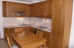 Кухня от масивен дъб с тъп ъгъл 93,8 градуса.Обзавеждането включва:кухня,уреди,голям шкаф в ниша,две маси и столове.