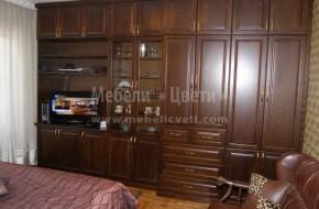 Голяма секция за спалня с място за книги и гардеробна част в която е прибрана прахосмукачка