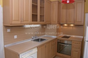 В двустаен панелен северен апартамент на първият етаж е монтирана ъглова кухня със светъл цвят на дървото,плота и гръбчето.