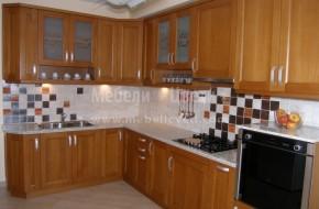 Кухня с масивни фризове на вратичките с ширина 80 мм. и табли от МДФ буков фурнир.Фурната е вградена на полуниво.В кухнята има шкаф за газова бутилка,която захранва с газ стъклокерамичния плот.