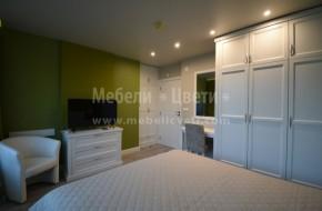 Обзавеждането на спалнята включва: легло с размер на матрака 1600/2000/240мм.,подматрачна рамка,матрак,две нощни шкафчета,трикрилен гардероб с надстройка,работна маса с огледало,вграден двукрилен гардероб с надсройка и скрин.