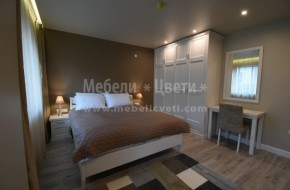 Обзавеждането на спалнята включва: легло за матрак 1640/1900,рамка,матрак,две нощни шкафчета,четирикрилен гардероб с надстройка,тоалетка и шкаф за телевизор. Гардеробът е с чекмеджета и вътрешно разпределение по желание на клиента.